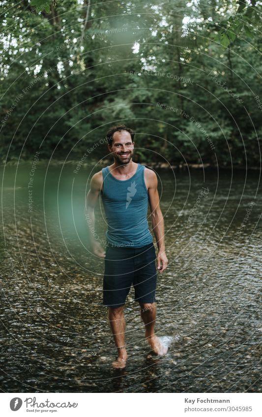 glücklicher Mann, der durch das Wasser eines Flusses watet 30s Erwachsener Vollbart sorgenfrei lässig Kaukasier heiter Selbstvertrauen selbstbewusst cool