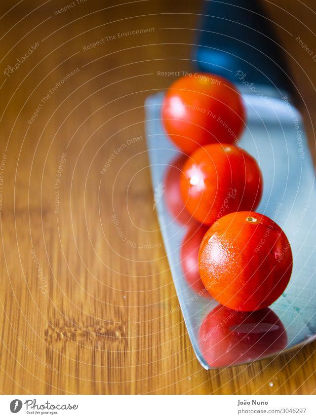Kirschtomaten über einem Kochmesser Gemüse Ernährung Mittagessen Bioprodukte Vegetarische Ernährung Diät Besteck Messer Metall Stahl Gleichgewicht Küchenchef
