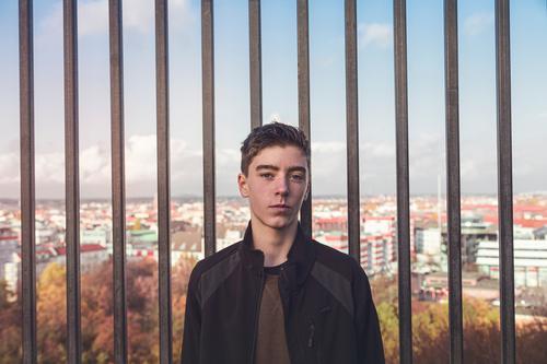 Porträt eines lächelnden jungen Mannes vor Bars und Berlin Architektur Herbst schön Borte Junge lässig Kaukasier selbstbewusst Europa Spaß Deutschland Raster