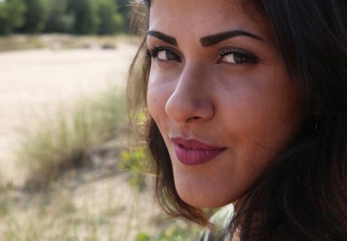 Estila feminin Frau Erwachsene 1 Mensch Sand Schönes Wetter Gras Wald brünett langhaarig beobachten Denken Lächeln Blick Willensstärke Wachsamkeit Neugier