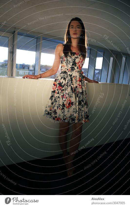 Junge Frau in Hotelflur Lifestyle Stil schön Leben Fensterfront Mauer Flur Jugendliche 18-30 Jahre Erwachsene Kleid Barfuß brünett langhaarig Beton stehen