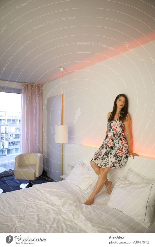 Junge Frau sitzt auf Hotelbett Lifestyle Stil Freude schön harmonisch Sessel Hotelzimmer Bett Jugendliche 18-30 Jahre Erwachsene Kleid Barfuß brünett langhaarig
