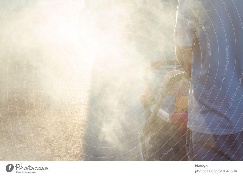 Vater schiebt baby im Buggy durch Rauch in die Sonne Mensch Baby Mann Erwachsene 2 gehen Verantwortung träumen Sorge Zukunftsangst Stress Verzweiflung Beginn