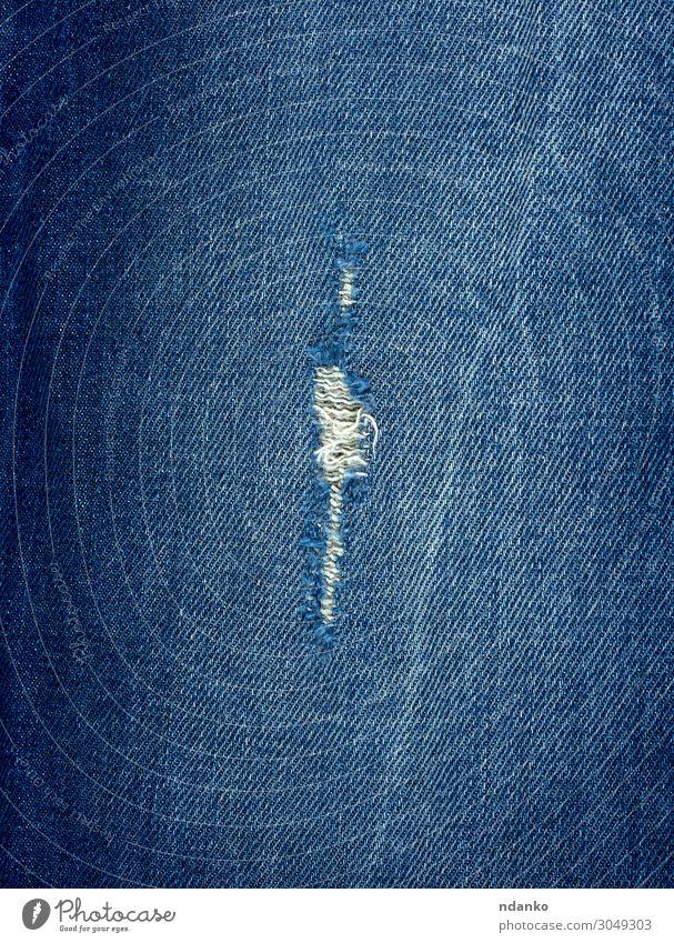 Fragment aus Blue Jeansstoff mit einem Loch Stil Design Mode Bekleidung Hose Jeanshose Stoff alt blau Farbe Hintergrund Leinwand lässig Baumwolle Schaden Sehne