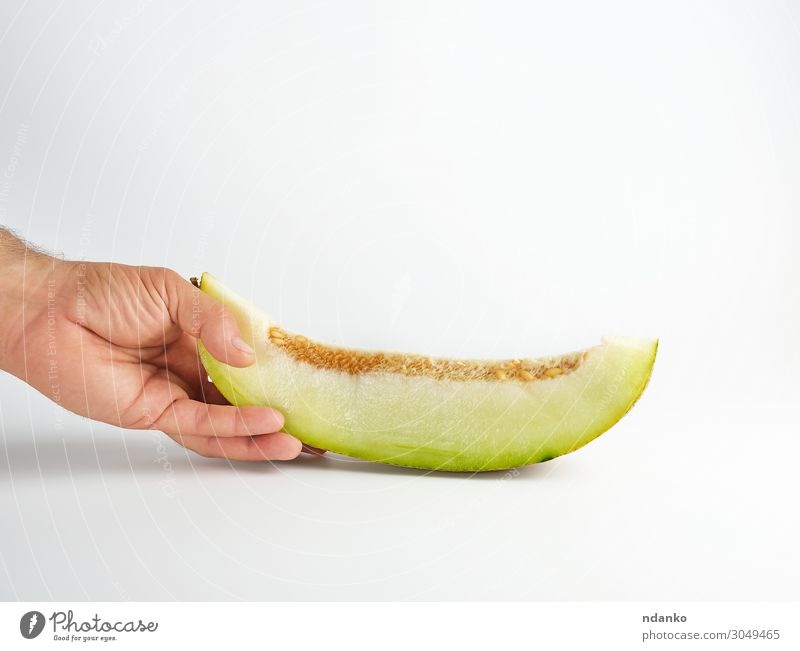 männliche Hand hält ein Stück reife Melone mit Samen. Gemüse Frucht Dessert Ernährung Vegetarische Ernährung Diät Sommer Natur Pflanze Essen frisch natürlich