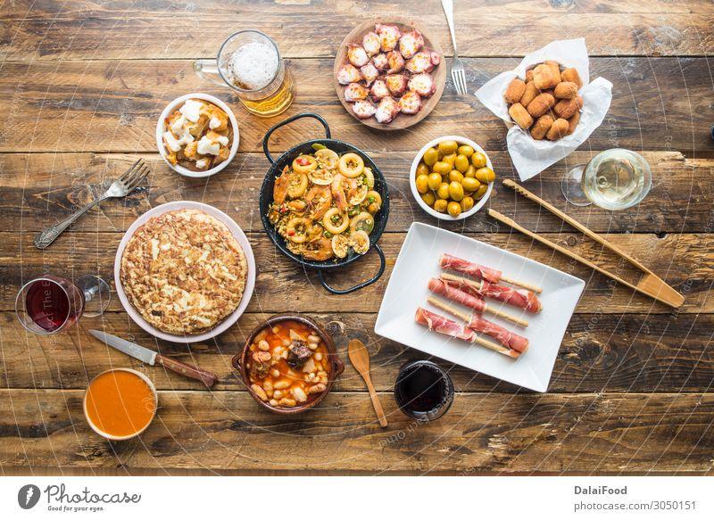 Typisches spanisches Essen Fleisch Meeresfrüchte Käse Brot Suppe Eintopf Ernährung Mittagessen Abendessen Bier Tisch Restaurant Holz frisch lecker oben schwarz