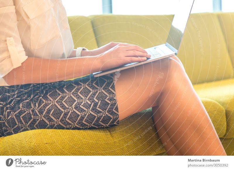 Geschäftsfrau, die an ihrem Laptob arbeitet, sitzt auf einer Couch. Glück schön Ferien & Urlaub & Reisen Sommer Arbeit & Erwerbstätigkeit Büro Business Computer