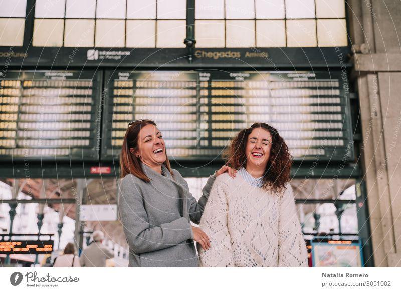 Zwei schöne Frauen, die am Bahnhof zusammen lachen. Lifestyle Glück Ferien & Urlaub & Reisen Tourismus Ausflug Ferne Erwachsene Freundschaft Verkehr