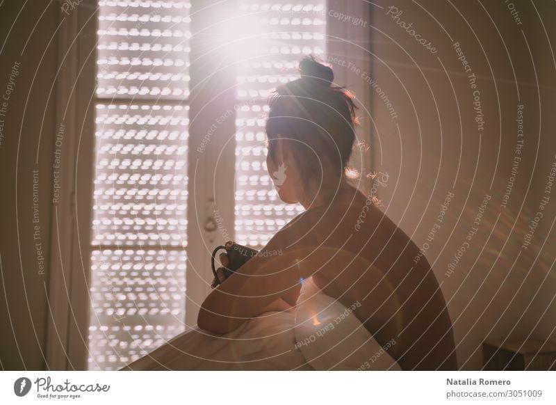 Eine Frau saß auf ihrem Bett und genoss eine Tasse Kaffee. Lifestyle Glück schön Körper Erholung Sonne Wohnung Schlafzimmer Erwachsene brünett schlafen Erotik