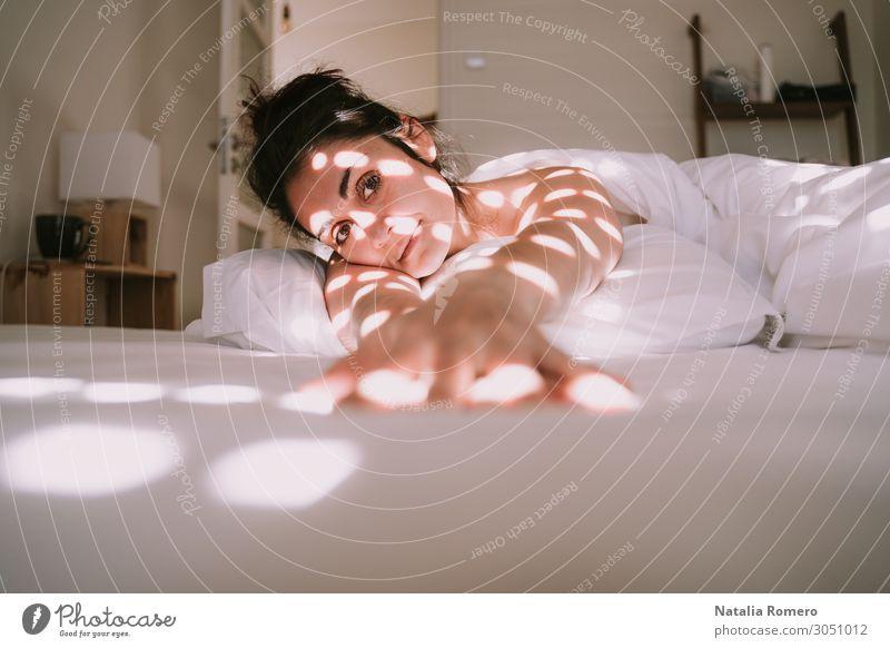Eine schöne Frau, die sich auf ihr Bett lehnt. Kaffee Lifestyle Glück Körper Erholung Sonne Wohnung Schlafzimmer Erwachsene brünett schlafen Erotik nackt