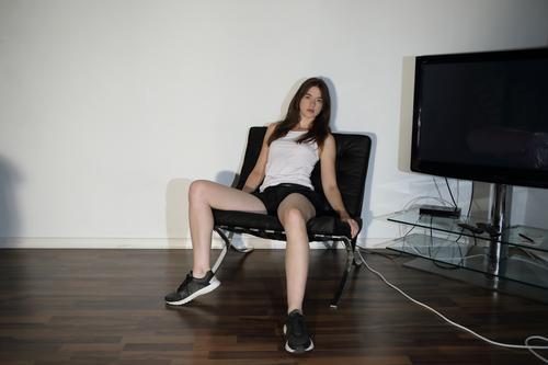 Junge Frau auf Sessel neben Fernseher Lifestyle Stil Leben Häusliches Leben Raum Klassische Moderne Jugendliche Beine 18-30 Jahre Erwachsene Jugendkultur