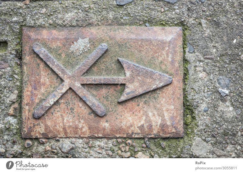 Kennzeichnung an einem Rangierbahnhof. Pfeil Kreuz Markierung Wegweiser Eisen Stahl Stein Beton Technik Gewicht Industrie Industrieanlage Schifffahrt Rost