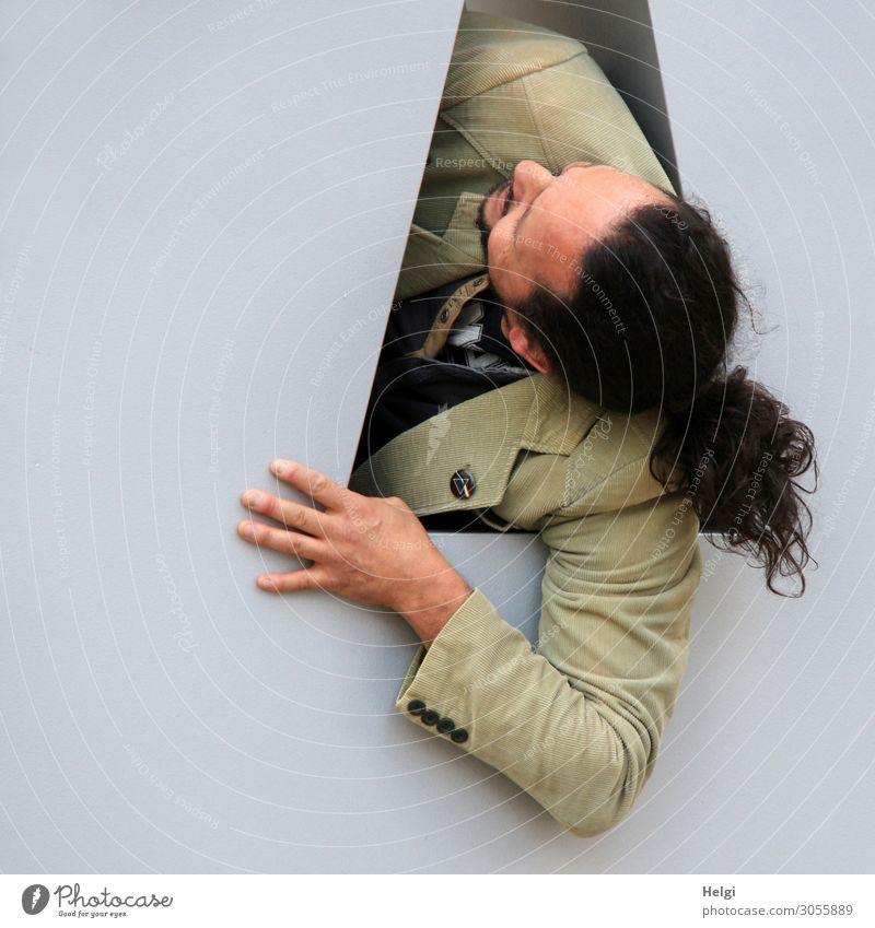 Porträt eines Mannes mit langen dunklen Haaren, Bart und beiger Jacke, der durch eine Öffnung nach oben schaut Mensch maskulin Erwachsene Kopf Haare & Frisuren