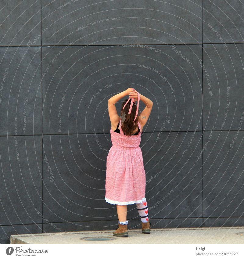 Rückansicht einer Frau mit brünetten langen Haaren, rosa Kleid und gemusterten Strümpfen steht mit erhobenen Armen vor einer dunkelgrauen Wand Mensch feminin