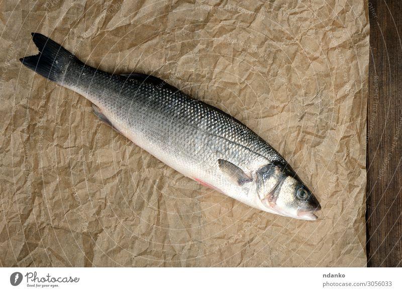frischer ganzer Seebarschfisch auf braunem Knitterpapier Fisch Meeresfrüchte Ernährung Abendessen Tisch Küche Natur Tier Papier Holz oben grau Gesundheit Bass
