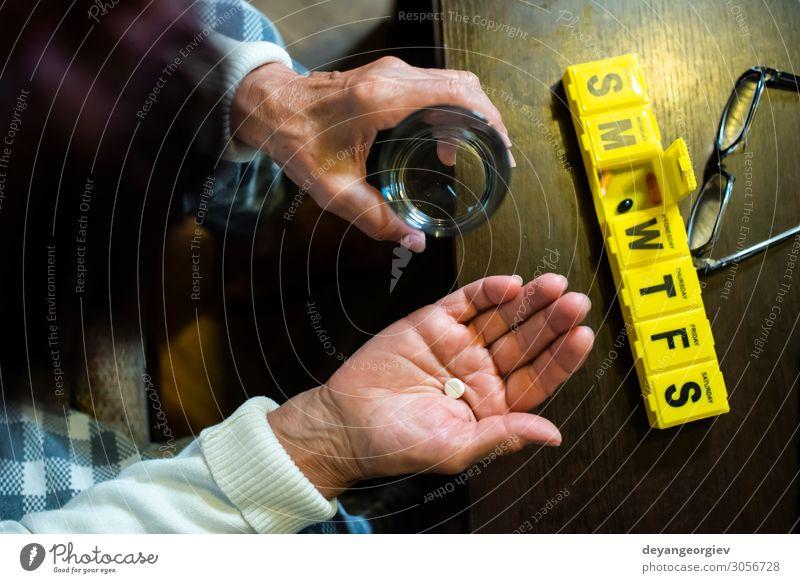 Ältere Frau nimmt Pillen aus der Schachtel. Gesundheits- und Seniorenkonzept Gesundheitswesen Krankheit Medikament Ruhestand Mensch Erwachsene Hand Zeitung