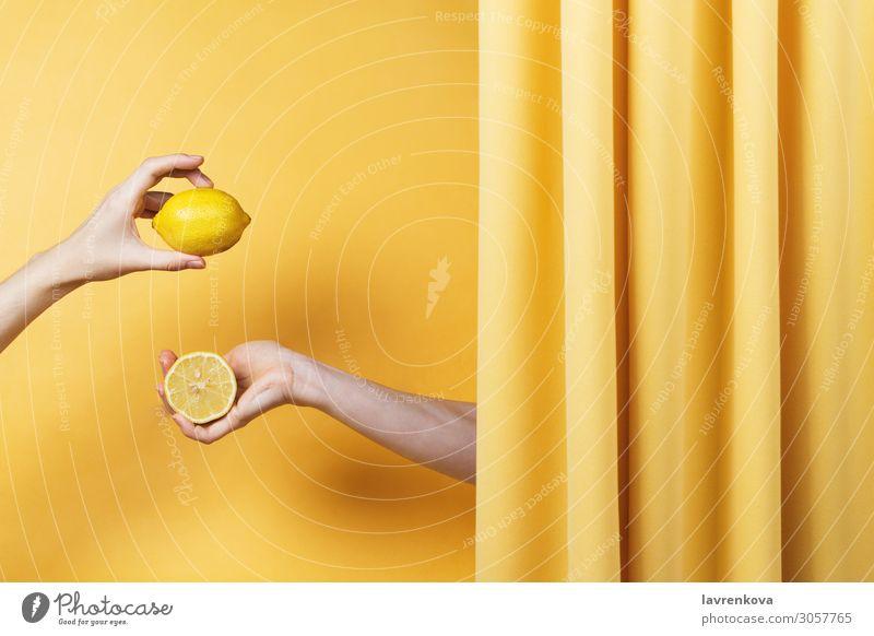 Zwei Frauenhände halten Schnitt und ganze Zitronen. natürlich gelb Finger Halt Hand Gesundheit Gesunde Ernährung Vitamin C Zitrusfrüchte Frucht Entwurf