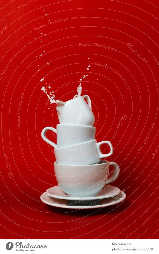 Tassen und Untertassen mit Milchkännchen oben und Spritzwasser innen Getränk Frühstück Kaffee Geschirr Tropfen Flüssigkeit liquide Morgen Bewegung Becher rot