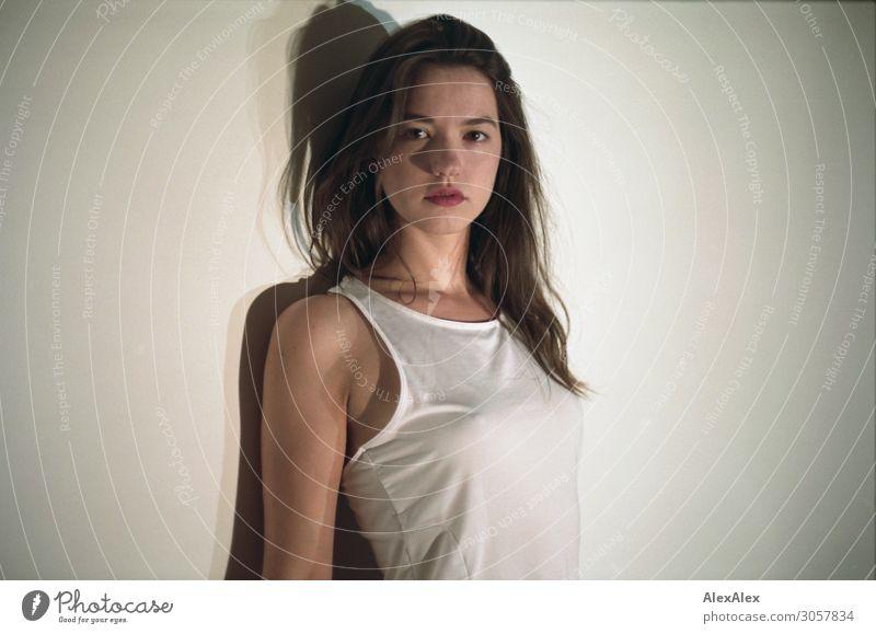 Portrait einer jungen Frau vor weißer Wand Lifestyle elegant Stil schön Wohlgefühl Vignettierung Raum Junge Frau Jugendliche 18-30 Jahre Erwachsene Trikot