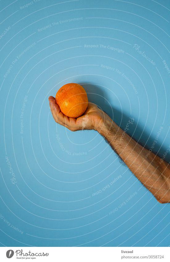 orange in der Hand an der blauen Wand Frucht Lifestyle Design Mensch Mann Erwachsene Arme Finger Natur genießen frisch Farbe Menschen Grafik u. Illustration