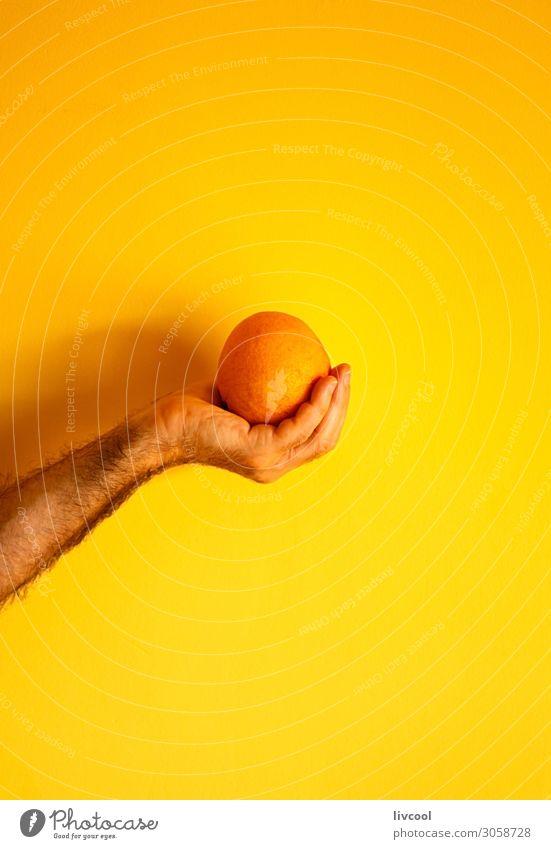 orange in der Hand an der gelben Wand Frucht Lifestyle Design Mensch Mann Erwachsene Arme Finger Natur genießen frisch Farbe Menschen Grafik u. Illustration