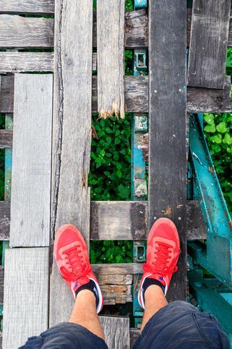 Watch your step! Brücke laufen Holz Holzbrücke Loch stolpern Stolperfalle bedrohlich gefährlich Absturz Absturzgefahr rot Schuhe Turnschuh Shorts Wade Fußtritt