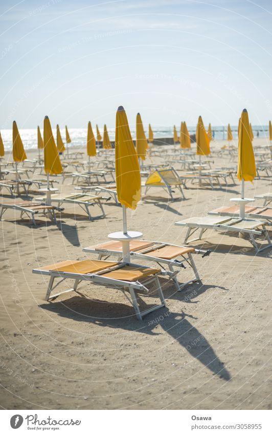 Verwaiste Sonnenliegen am Strand Urlaub Meer Mittelmeer Tourismus Massentourismus Leere menschenleer Liege Strandliege Sonnenschirm Sonnig Warm Abend Sand