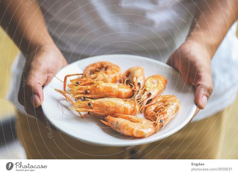 Hand haltend Garnelen gegrillt Garnelen gekocht in den Meeresfrüchten gekocht Ernährung Essen Mittagessen Abendessen Teller Restaurant frisch lecker grün rot