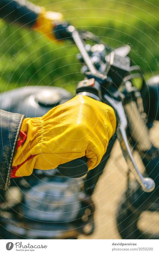 Bikerhand mit Handschuhen, die den Lenker greifen. Lifestyle Motor Mensch Mann Erwachsene Gras Verkehr Straße Fahrzeug Motorrad authentisch retro gelb
