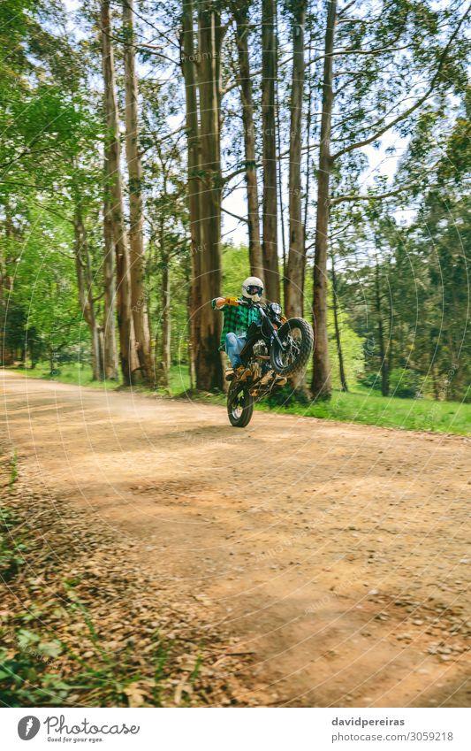 Mann mit Helm auf einem Custom-Motorrad Lifestyle Mensch Erwachsene Baum Gras Verkehr Straße Wege & Pfade Fahrzeug Jeanshose Handschuhe warten authentisch retro