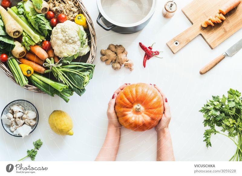 Frauenhände halten Kürbis auf weißem Küchentisch Lebensmittel Gemüse Ernährung Bioprodukte Vegetarische Ernährung Diät Geschirr Topf Lifestyle kaufen Stil