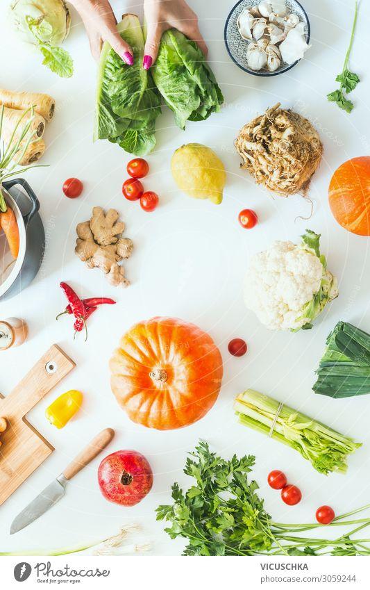 Weibliche Hände halten Salat auf weißem Tischhintergrund mit Kürbissen und verschiedenen Gemüsesorten der Saison, Topf, Schneidebrett und Messer. Kochen der Ernte. Flach liegend. Gesunde Lebensweise und Ernährung. Kohlenhydratarm