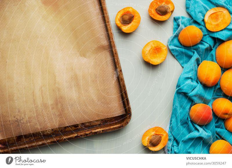 Lebensmittelhintergrund mit frischem ganzen und halbierten Aprikosenstrauß und leerem Backblech, Ansicht von oben. Konzept für saisonale Früchte. Haufen