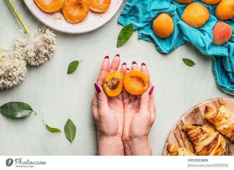 Hände halten halbierte Aprikose mit Kern Lebensmittel Frucht Croissant Ernährung Geschirr Stil Mensch Frau Erwachsene Hand Design Teilung Kerne stoppen