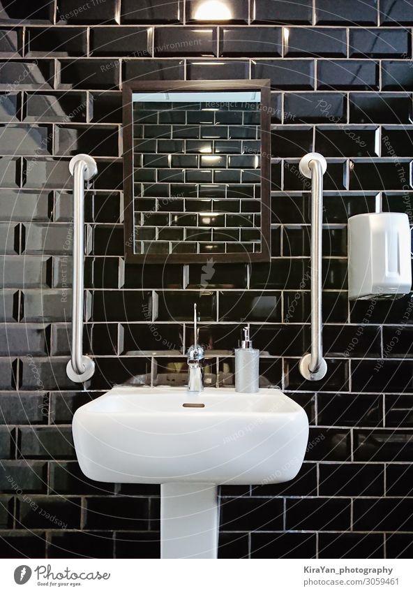 Modernes Design des Toilettenraumes mit schwarzen, glänzenden Fliesen. Schwarze Glanzfliese für zeitgenössisches Dekorationsdesign. Abstrakter Fliesenhintergrund für die Heimdekoration