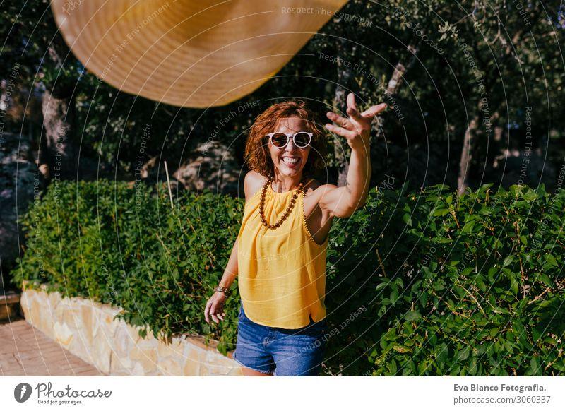 Hübsches Mädchen bei Sonnenuntergang, das einen Hut in der Hand hält und ihn in die Kamera wirft. Sommer, Spaß und Lifestyle im Freien Freiheit Mensch Lächeln