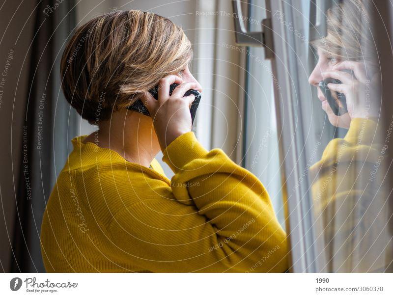 Mädchen am Telefon, das aus dem Fenster schaut. Lifestyle Handy Mensch feminin Junge Frau Jugendliche 1 18-30 Jahre Erwachsene Pullover Strickpullover blond