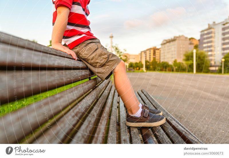 Jungenbeine, die auf der Oberseite des Bankparks sitzen, entspannen sich. Lifestyle schön Erholung Sommer Garten Kind Mensch Kindheit Fuß Natur Park Hose Schuhe
