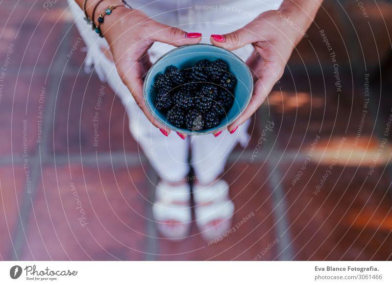 eine junge Frau, die eine Schüssel Brombeeren hält. Sie bereitet ein gesundes Rezept aus verschiedenen Früchten, Wassermelone, Orange und Brombeeren zu. Verwendung eines Mixers. Hausgemacht, drinnen, gesunde Lebensweise