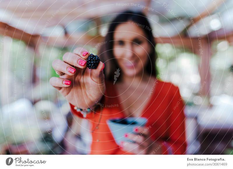 eine junge Frau, die eine Schüssel Brombeeren hält. Sie bereitet ein gesundes Rezept aus verschiedenen Früchten, Wassermelone, Orange und Brombeeren zu. Verwendung eines Mixers. Hausgemacht, drinnen, gesunder Lebensstil. selektiver Fokus