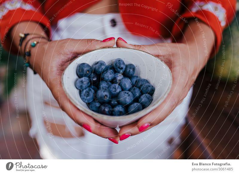 eine junge Frau, die eine Schüssel mit Blaubeeren hält. Sie bereitet ein gesundes Rezept mit verschiedenen Früchten, Wassermelone, Orange und Brombeeren vor. Verwendung eines Mixers. Hausgemacht, drinnen, gesunde Lebensweise