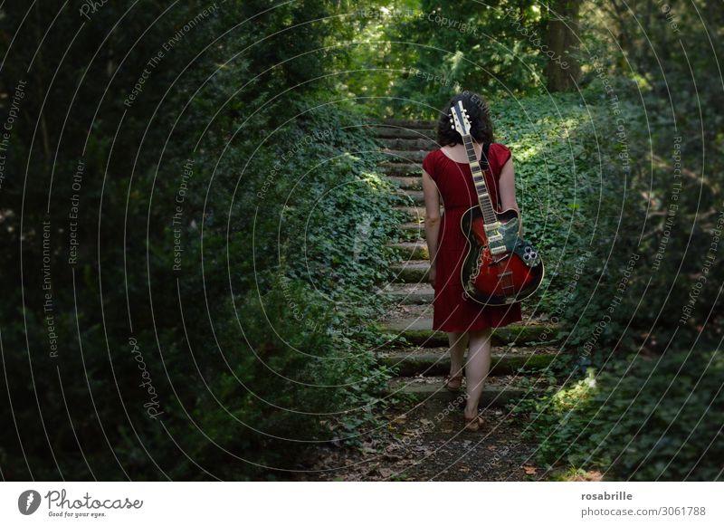 on the road again - musikalischer Aufstieg - brünette junge Frau geht mit roter Gitarre auf dem Rücken durch den Wald   allein mit Gitarre im Wald