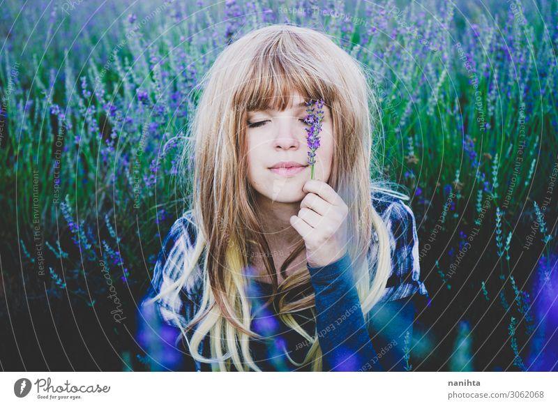 Junge Frau genießt den Tag in einem Lavendelfeld. Kräuter & Gewürze Lifestyle schön Gesicht Kosmetik Alternativmedizin Medikament Leben Erholung Mensch feminin