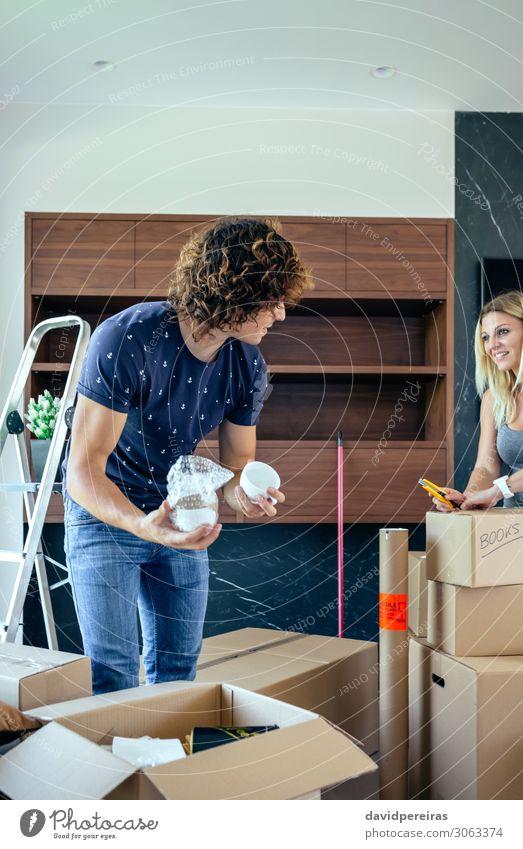 Koppeln Sie das Auspacken von Umzugskartons. Lifestyle Glück schön Wohnung Haus Umzug (Wohnungswechsel) Wohnzimmer Mensch Frau Erwachsene Mann
