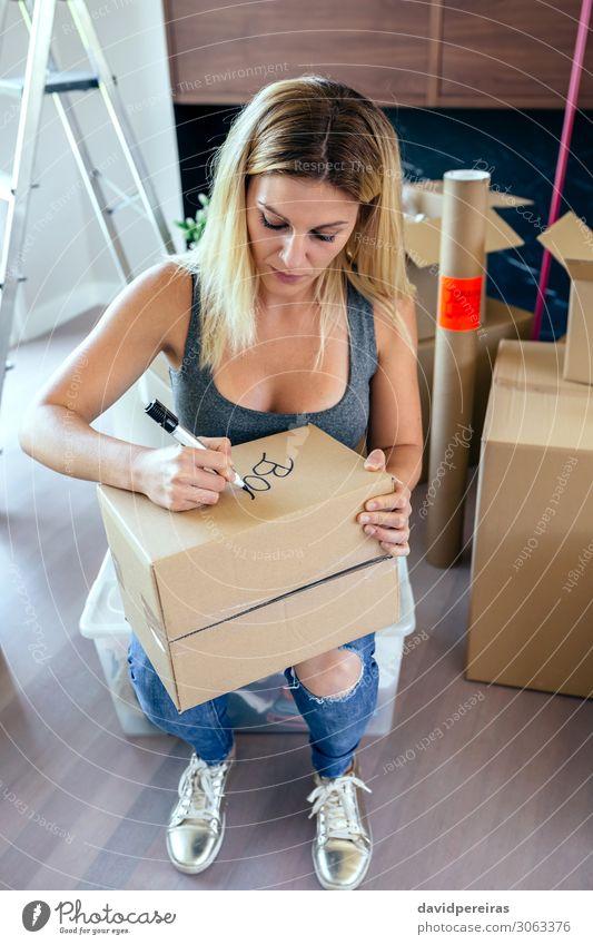 Sitzende Frau beim Beschriften von Umzugskartons Lifestyle schön Wohnung Haus Umzug (Wohnungswechsel) Wohnzimmer Arbeit & Erwerbstätigkeit Mensch Erwachsene