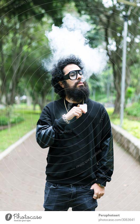 Junger Mann raucht eine elektronische Zigarette im Park. Lifestyle Sommer Jugendliche Erwachsene Sonnenbrille Vollbart rot Raps lässig Rauch Verdunstung vaping