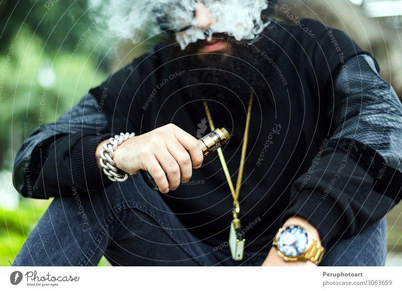 Mann mit Bart raucht eine elektronische Zigarette. Lifestyle Mensch Erwachsene Hand Natur Park Mode Bekleidung Sonnenbrille Hut Vollbart sitzen Coolness modern