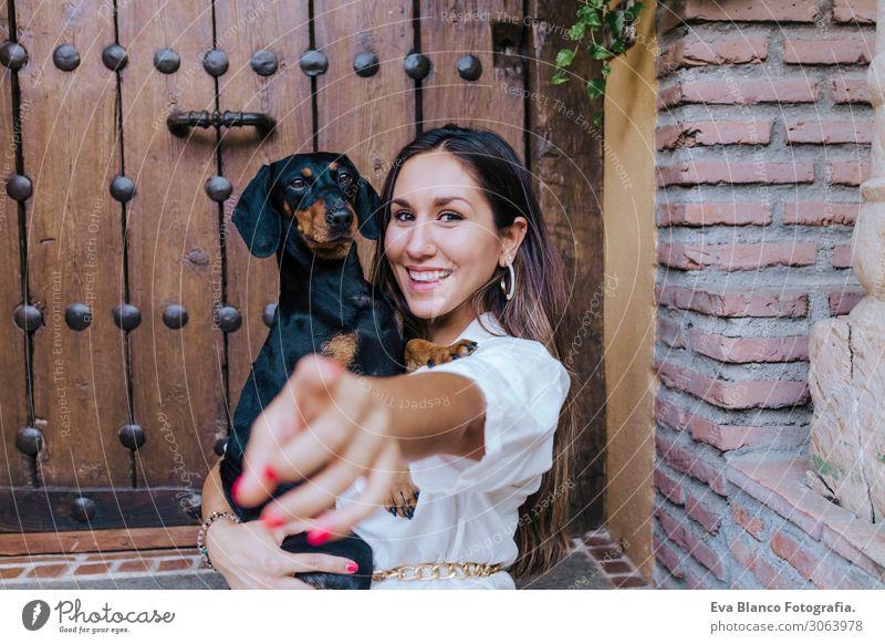 süßer kleiner Würstchenhund sitzend mit ihrer Besitzerin zu Hause Wurstwaren Lifestyle Glück schön Körper Erholung Massage Freizeit & Hobby