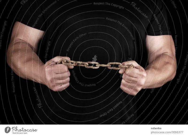 Erwachsener Mann in schwarzer Kleidung steht aufrecht mit angespannten Muskeln. Freiheit Mensch Hand 30-45 Jahre Metall Stahl Sport stehen dunkel stark Kraft