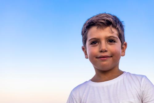 Schönes Gesicht eines kleinen Kindes gegen den blauen Himmel Lifestyle Freude Glück Freizeit & Hobby Ferien & Urlaub & Reisen Sommer Insel Erfolg Mensch
